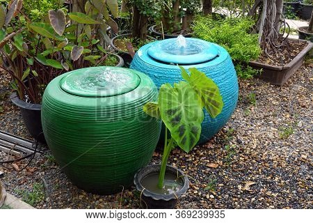 Green Jar And Blue Jar Of Water Springing.,jar With Flowing Water Spring In The Garden. Water Overfl