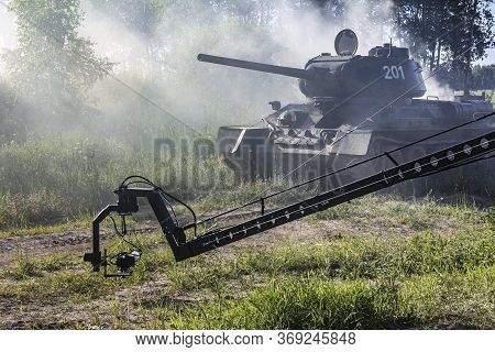 Filming A Tank Shrouded In Smoke. Soviet Tank T-34 On The Move. Cameras Filming The Tank. A War Scen