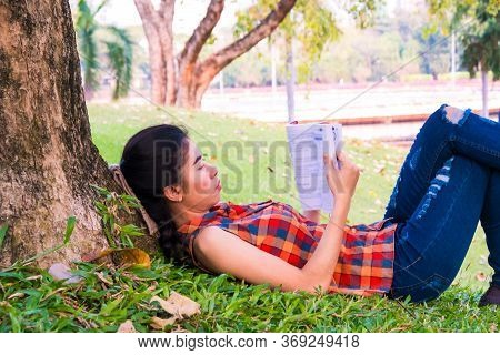 Asian Women Reading Under Tree At Public Park Relax And Intend To Study Knowledge In The Holiday On