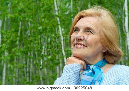 Pretty old woman is enjoying the air