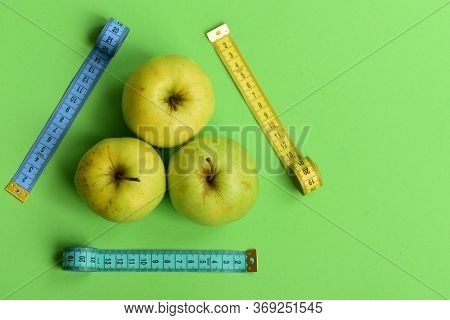 Apples Near Measuring Tapes Trio On Green Background, Top View