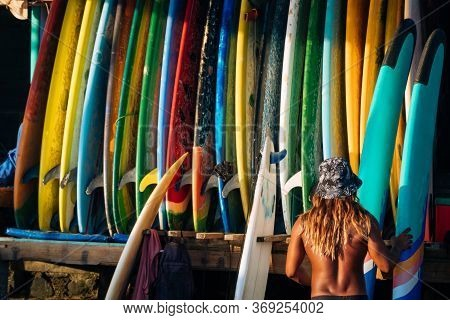 Set Of Different Color Surf Boards In A Stack By Ocean With Unrecognizable Man Choosing Board. Bali.