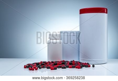 Antibiotic Capsule Pills Spread On White Table And Plastic Drug Bottle White Blank Label. Antibiotic