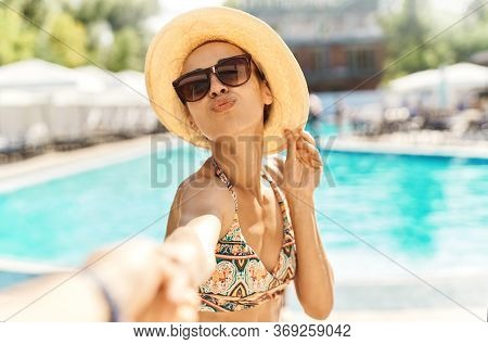 Funny Smiling Woman In Hat And Sunglasses Holding Someone Hand And Sending Kiss To Camera Against Sw