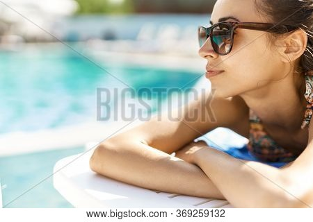 Close-up Portrait Of Leisure Women In Sunglasses Sunbathing Near Pool.
