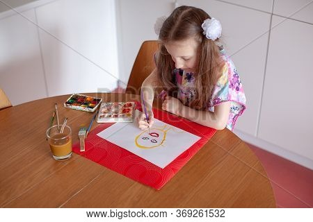 7 Years Old Girl Painting With Watercolor In The Kitchen. Home Interior.