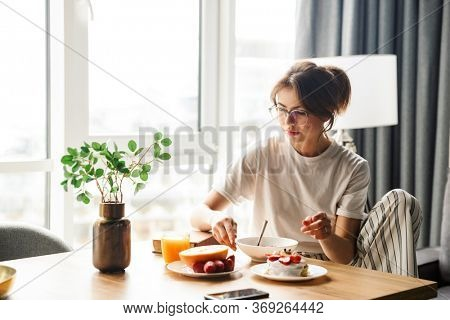 Photo of young serious woman eating fruits and pancakes while having breakfast in cozy room at home