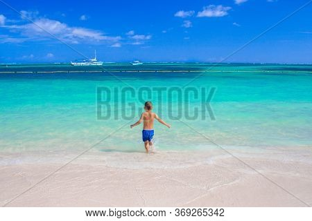 A 5 Year Old Boy Enters The Calm And Beautiful Sea Alone. European Child On The Background Of The Ca