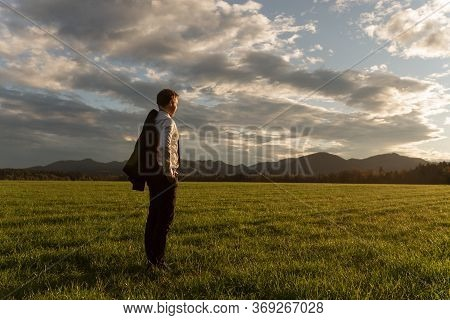 Young Businessman With His Suit Jacket Over The Shoulder, Standing In Beautiful Green Meadow Under D