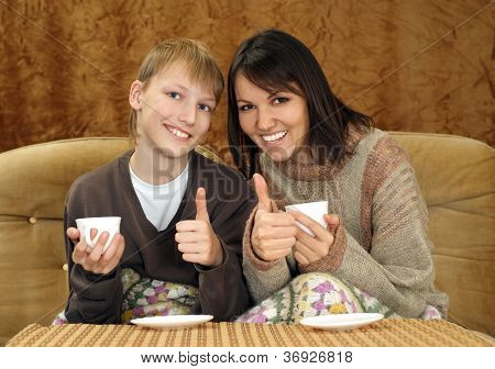 Beautiful mum and son sitting on the couch with a cup