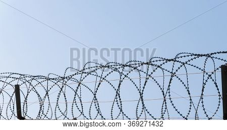 Wire And Barbed Wire Fence With Blue Sunset Sky In The Background