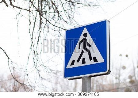 Pedestrian Crossing Sign. Closeup Of Pedestrian Crossing Sign Against A Sky. Direction Sign Pedestri