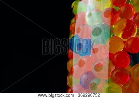 Multi-colored Silicone Gel Balls In A Glass On A Black Background