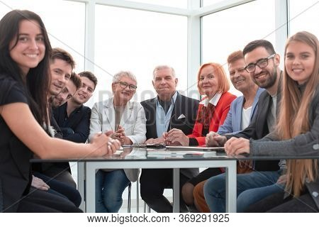 Happy business people sitting around the table