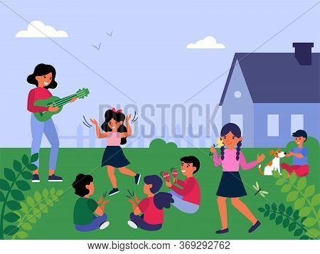 Female Teacher Playing Guitar To Children Playing Outside. Babysitter Having Fun With Kids Outdoors