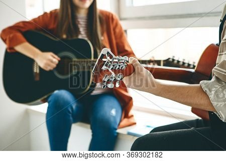 Learning To Play The Guitar. The Teacher Explains To The Student The Basics Of Playing The Guitar. I