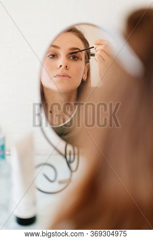 Beautiful Girl Doing Make-up And Looks In The Mirror. Care Of Yourself.