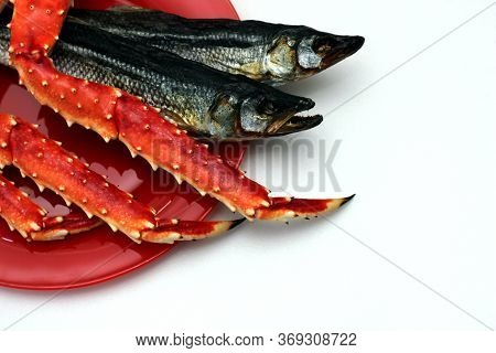Cooked Kamchatka Crab And Dried Salted Fish On A Red Plate. Beer Snack. Seafood.