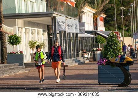 Calvia, Majorca, Spain - June 1, 2020:  Two Boys Walking In The Commercial Area Of Port Adriano, The