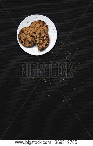 Chocolate Chip Cookies In A White Plate, On Black Fabric Background Full Of Crumbles And Chocolate C