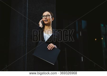 Young Business Woman In A Black Skirt And Jacket On The Street Near The Office Building