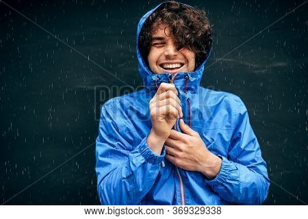 Portrait Of The Man Smiling Broadly, Wearing Blue Raincoat During Rain Outside. Handsome Male In Blu
