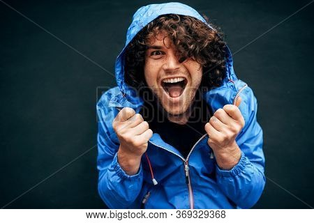 Outdoor Portrait Of Amazed Man Smiling Broadly, Wearing Blue Raincoat During Rain Outside. Handsome