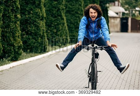 Outdoor Horizontal Image Of Happy Man Smiling Broadly During Cycling On His Bike Down The Street. Ch