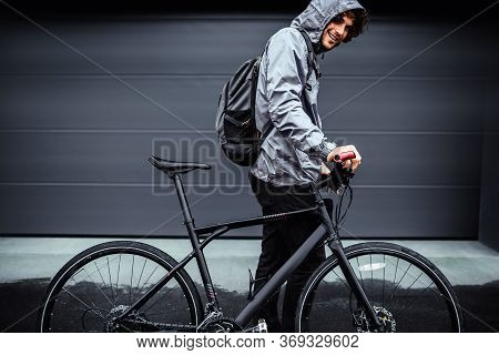 Outdoor Side View Image Of A Handsome Man Posing With His Bike Before Bicycling On A Rainy Day Next