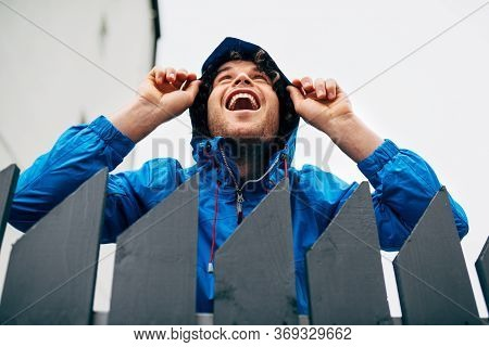 Horizontal Outdoor Image Of Happy Man Smiling Broadly, Wearing Blue Raincoat With Hoody On The Head