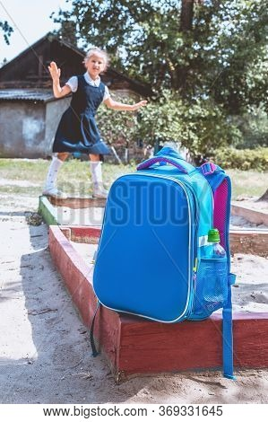 Back To School Concept. A School Backpack In The Foreground And A Junior Schoolgirl On The Playgroun