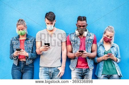 Multiracial Friends With Face Masks Using Tracking App With Mobile Smart Phones - Young Millenial Pe
