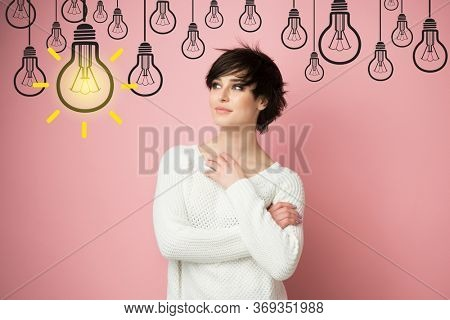Beautiful young woman looking at light idea bulb above head, pink background and copyspace. Pretty brunette model and cartoon lamp. Girl thinks, solves a difficult problem and finds brilliant solution