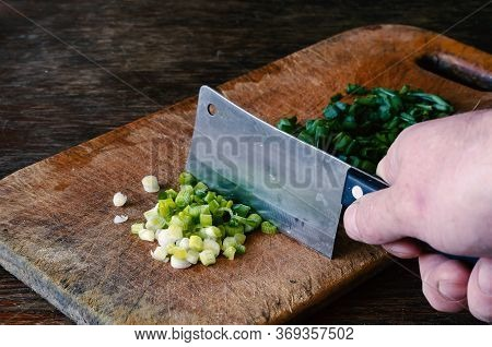 A Man With A Kitchen Hatchet Grinds A Scallion On A Cutting Board. Group Of Fresh Chopped Lettuce On