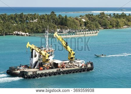 The Tugboat With Cranes Traveling Inside Nassau Harbour Along Paradise Island Coastline (bahamas).
