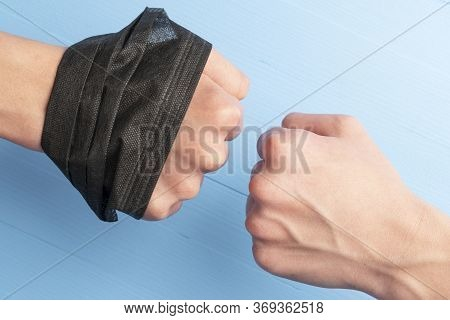 Fist With A Black Mask In His Hand Against Another Fist On A Blue Background Close-up. Symbol Of Pro