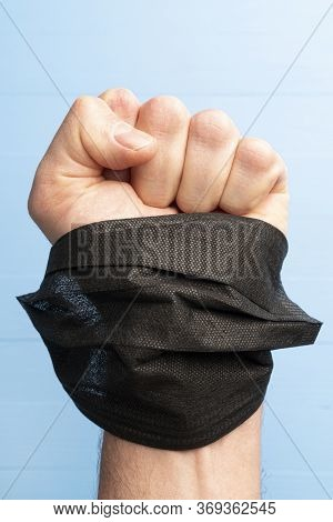 Black Lives Matter Concept. Fist With A Black Mask In Hand On A Blue Background Close-up. Symbol Of