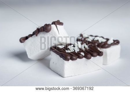 White Marshmallow Poured By Dark Chocolate. A Few Marshmallows On A White Background. Sweet Cuisine
