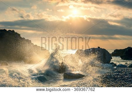 Big Wave hit the rock at beach, sea water splash up to the sky with sun. Sunset Sundown at Sea. Storm. Seascape.