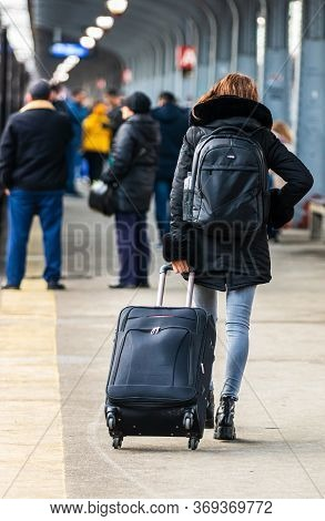Travelers And Commuters Carry Luggage And Backpacks On The Train Platform Of Bucharest North Railway