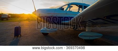 A Blue Suitcase And A Parked Small Private Jet. Quadruple Plane With A Propeller For An Air Taxi In