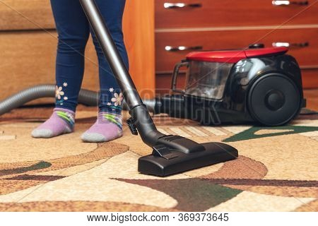 A Small Child Vacuums A Carpet With A Vacuum Cleaner