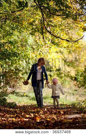 Mother And Daughter Walking In The Forest