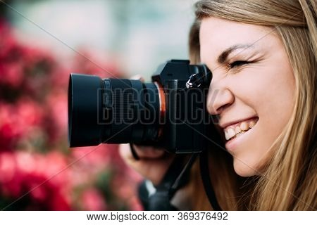 Young Cute Girl Photographer Holds A Camera Near The Face Photographing People