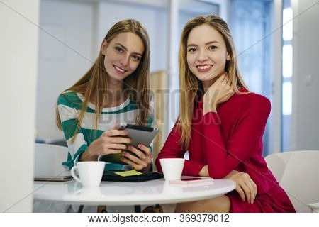 Pensive Best Friends Using Touchpad For Cheesing Web Store For Online Shopping Sitting In Cafe
