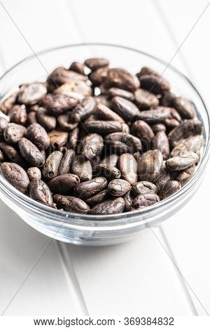 Cocoa beans on glass bowl on white table.