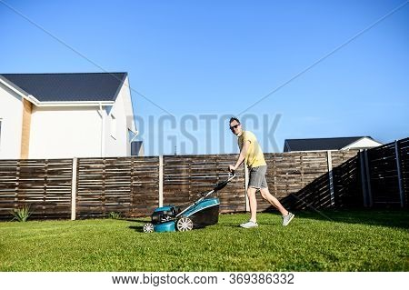A Young Man Mows A Lawn With A Lawn Mower. Garden Works In The Backyard, Maintenance Of The House Ar