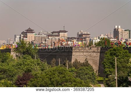 Xian, China - April 30, 2010: North Gate Of Huancheng City Wall. Men Ramparts Behind Green Foliage W