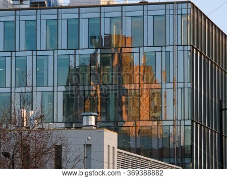 Reflection Of The Old Building In The Glass Cladding Of A Modern Building
