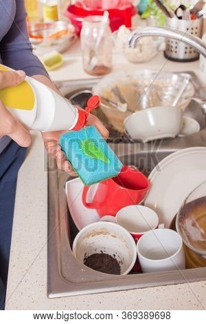 A Woman's Hand Holds A Dishwashing Sponge Onto Which A Dishwashing Liquid Is Poured From A White Bot